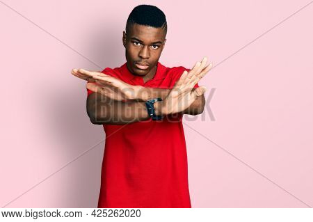 Young african american man wearing casual red t shirt rejection expression crossing arms and palms doing negative sign, angry face