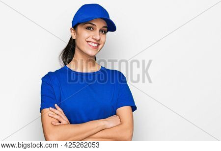 Young hispanic girl wearing delivery courier uniform happy face smiling with crossed arms looking at the camera. positive person.