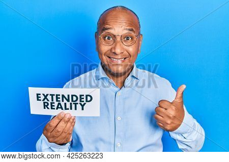 Middle age latin man holding paper with extended reality message smiling happy and positive, thumb up doing excellent and approval sign