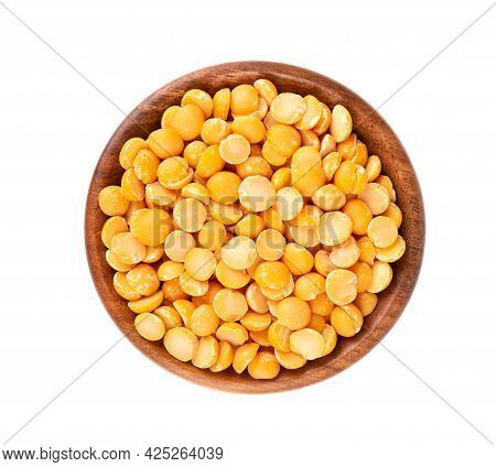 Dry Yellow Split Peas In Wooden Bowl, Isolated On White Background. Halves Of Yellow Legume Peas. To