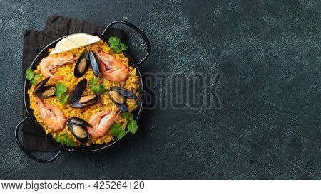 Traditional Spanish Seafood Paella In Pan With Chickpeas, Shrimps, Mussels, Squid On Black Concrete