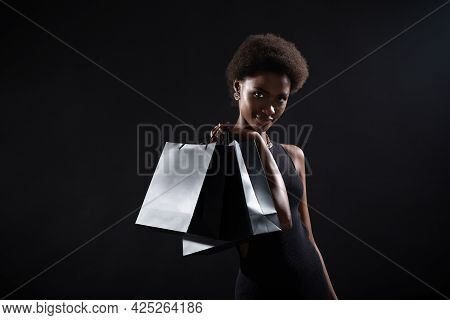 Black Friday Concept. African American Woman Hold Black Shopping Bags On Black Background