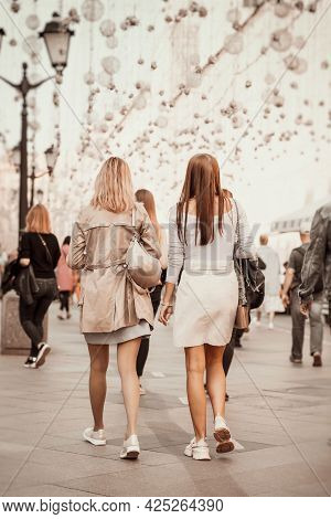 Unrecognizable Girls Walking On City Street, View From Behind. Modern Lifestyle. Regular People Out