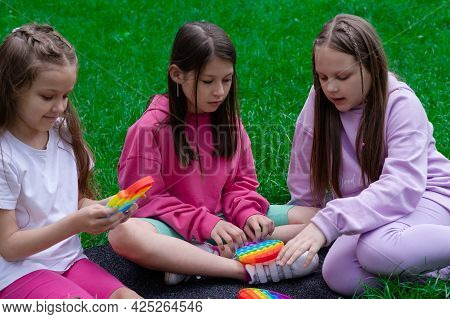 Three Teenage Girls Play With Trendy Sensory Toy Pop It Outdoors On Grass. Push Pop Bubble Flexible