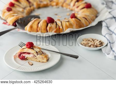 A Freshly Baked Raspberry Crescent Ring With A Slice Out In Front Ready For Eating.