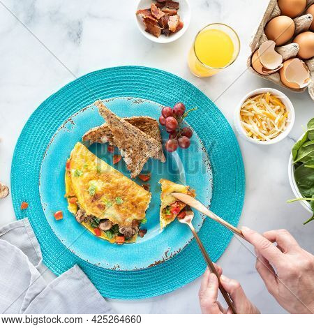 Freshly Made Omelette Served With Toast And Orange Juice With Hands Using Cutlery To Cut A Piece.