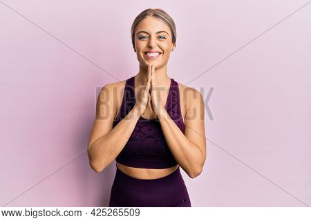 Beautiful blonde woman wearing sportswear over pink background praying with hands together asking for forgiveness smiling confident.