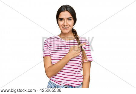 Young hispanic woman wearing casual clothes cheerful with a smile of face pointing with hand and finger up to the side with happy and natural expression on face