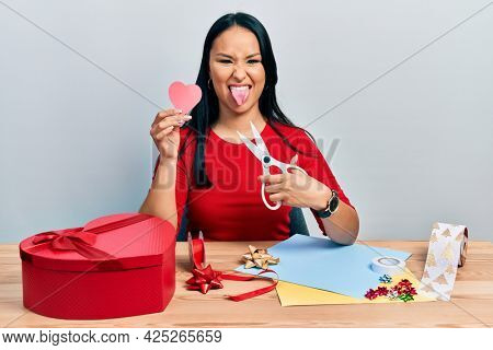 Beautiful hispanic woman with nose piercing doing handcraft heart sticking tongue out happy with funny expression.