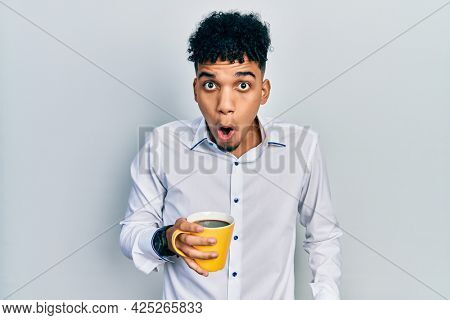 Young african american man drinking a cup of coffee scared and amazed with open mouth for surprise, disbelief face