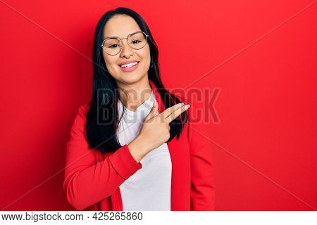 Beautiful hispanic woman with nose piercing wearing casual look and glasses cheerful with a smile of face pointing with hand and finger up to the side with happy and natural expression on face