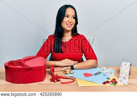 Beautiful hispanic woman with nose piercing doing handcraft creative decoration looking away to side with smile on face, natural expression. laughing confident.