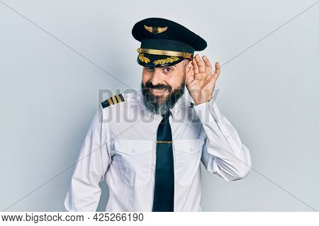 Young hispanic man wearing airplane pilot uniform smiling with hand over ear listening an hearing to rumor or gossip. deafness concept.