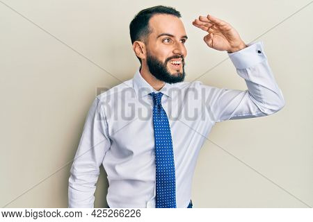 Young man with beard wearing business tie very happy and smiling looking far away with hand over head. searching concept.