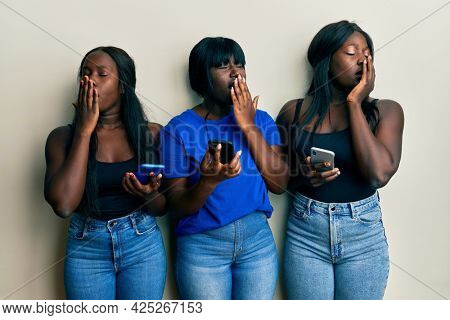 Three young african american friends using smartphone bored yawning tired covering mouth with hand. restless and sleepiness.