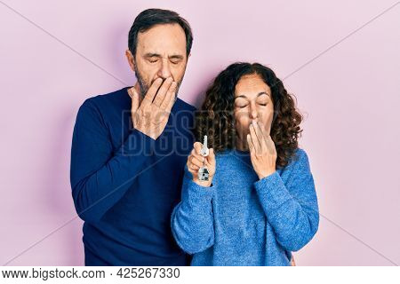 Middle age couple of hispanic woman and man holding keys of new home bored yawning tired covering mouth with hand. restless and sleepiness.