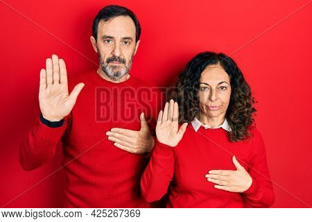 Middle age couple of hispanic woman and man hugging and standing together swearing with hand on chest and open palm, making a loyalty promise oath