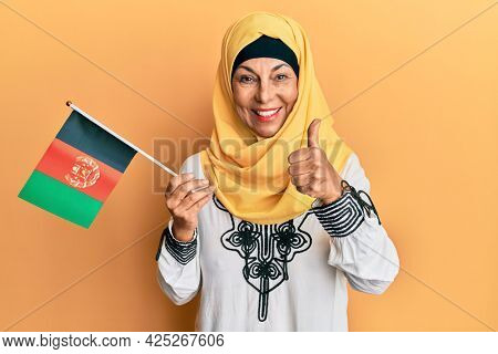 Middle age hispanic woman holding afghanistan flag smiling happy and positive, thumb up doing excellent and approval sign