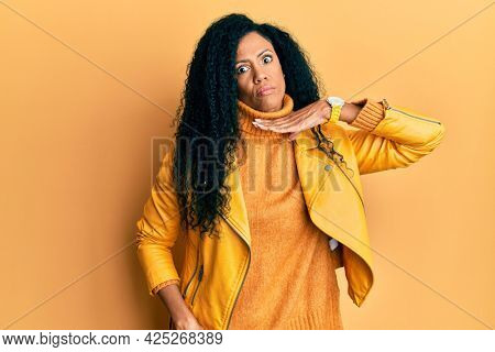 Middle age african american woman wearing wool winter sweater and leather jacket cutting throat with hand as knife, threaten aggression with furious violence