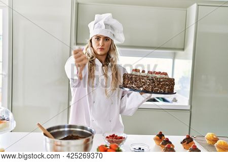 Young caucasian pastry chef woman cooking pastries and cake at the kitchen with angry face, negative sign showing dislike with thumbs down, rejection concept