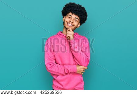 Young african american man with afro hair wearing casual pink sweatshirt looking confident at the camera smiling with crossed arms and hand raised on chin. thinking positive.