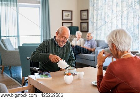 Smiling senior man pouring tea in cup from teapot in care facility with wife sitting at table in the common area. Elderly man in care centre sitting on wheelchair serving tea during a visit.