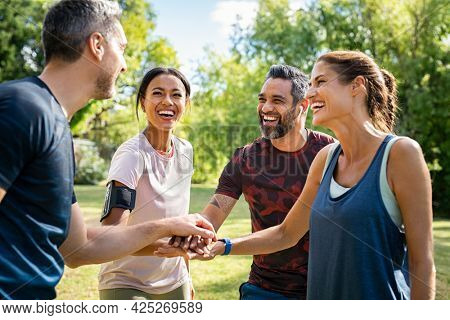 Laughing mature and multiethnic sports people at park. Happy group of men and women smiling and stacking hands outdoor after fitness training. Mature sweaty team cheering after intense training.