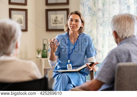 Nurse explaining to seniors at nursing home. Group of old men and women listening to young nurse on the change of therapy. Psychological support with counsellor therapist for a group of elderly people