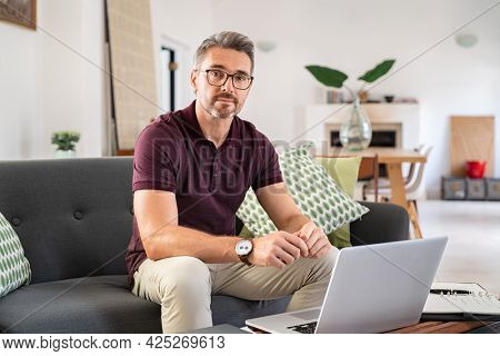 Portrait of mature man wearing spectacles and working from home. Mid adult man sitting on sofa while working on laptop and looking at camera. Businessman using laptop in telecommuting from home.