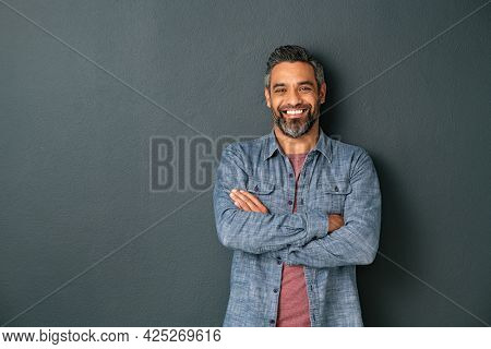Handsome mid adult man with beard and crossed arms looking at camera. Mature middle eastern man isolated against grey wall and smiling. Satisfied indian guy looking at camera with a big laugh.