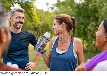 Sporty middle aged woman drinking water from bottle after fitness exercise. Latin mature woman drinking water for refreshment after workout in park while talking and smiling with a group of friends.