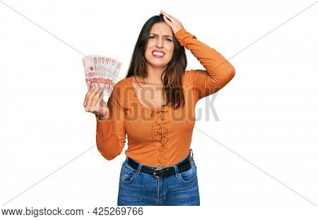 Beautiful hispanic woman holding 10 colombian pesos banknotes stressed and frustrated with hand on head, surprised and angry face