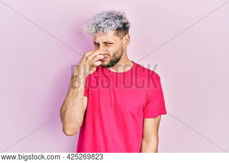Young hispanic man with modern dyed hair wearing casual pink t shirt smelling something stinky and disgusting, intolerable smell, holding breath with fingers on nose. bad smell