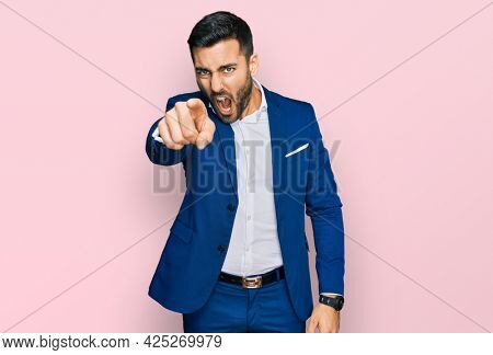 Young hispanic man wearing business jacket pointing displeased and frustrated to the camera, angry and furious with you