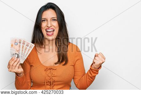 Beautiful hispanic woman holding 10 united kingdom pounds banknotes screaming proud, celebrating victory and success very excited with raised arms