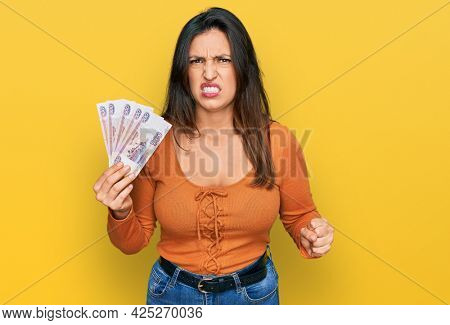 Beautiful hispanic woman holding russian 500 ruble banknotes annoyed and frustrated shouting with anger, yelling crazy with anger and hand raised