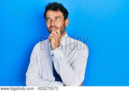 Handsome man with beard wearing business shirt and tie thinking concentrated about doubt with finger on chin and looking up wondering