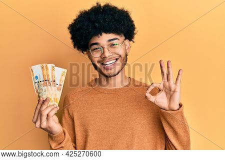 Young african american man with afro hair holding 500 philippine peso banknotes doing ok sign with fingers, smiling friendly gesturing excellent symbol