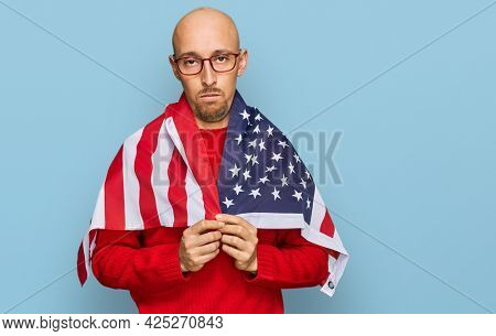 Bald man with beard wrapped around united states flag thinking attitude and sober expression looking self confident