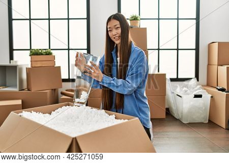Young chinese girl smiling happy unboxing cardboard package at new home