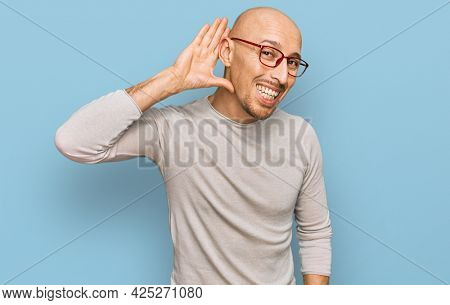 Bald man with beard wearing casual clothes and glasses smiling with hand over ear listening an hearing to rumor or gossip. deafness concept.