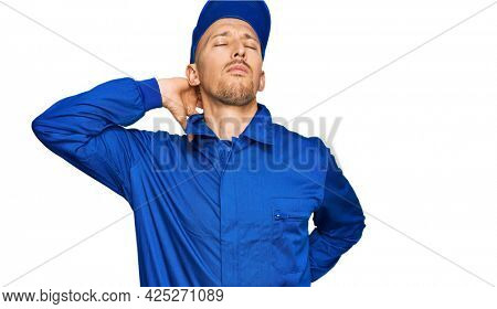 Bald man with beard wearing builder jumpsuit uniform suffering of neck ache injury, touching neck with hand, muscular pain