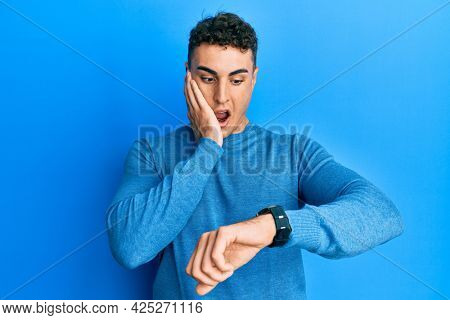 Hispanic young man wearing casual winter sweater looking at the watch time worried, afraid of getting late