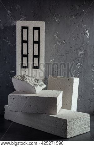Aerated concrete block cube or bricks near plaster wall background texture. Construction concept of minimalism design