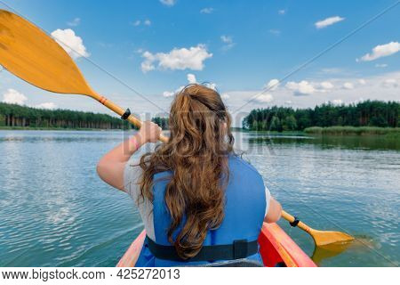 long-haired brunette woman paddles a kayak across a lake, back view