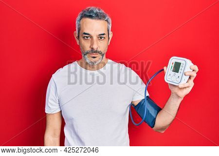 Handsome middle age man with grey hair using blood pressure monitor thinking attitude and sober expression looking self confident