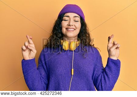 Young brunette woman with curly hair listening to music using headphones gesturing finger crossed smiling with hope and eyes closed. luck and superstitious concept.