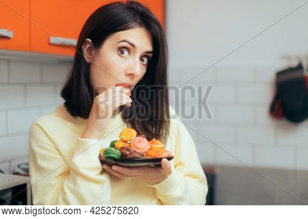 Woman Eating Macarons Feeling Guilty And Hiding