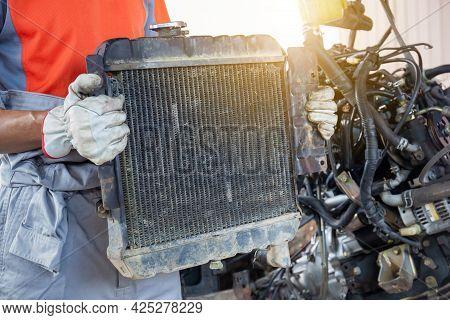 Auto Mechanics Holding Broken Car Radiator In Auto Service, Technician Doing The Checklist For Repai