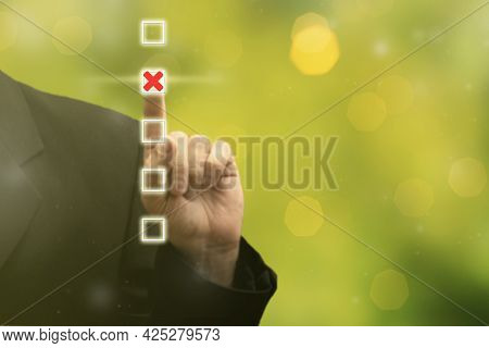 Businessman Hand Touching And Pointing Right Choice Marked With Red Cross, Best Option On Blurred Gr